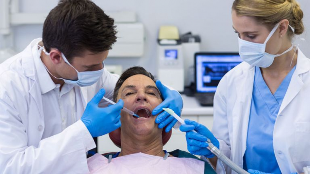 Dentist injecting anesthesia on man's mouth San Leandro